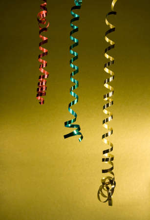 Sparkling tinsel streamers on a gold background, design element or background. Stock Photo
