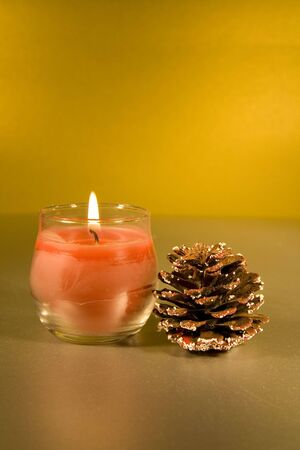 Christmas decorations with lit Candle on a golden background... photo