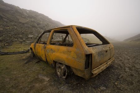 burnt out: Burnt out and rusted car, stolen and dumped on the moor. Stock Photo