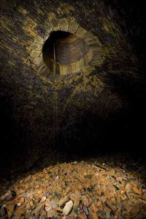 Old ventilation shaft and rubble in Tunnel Underground Light painting in disused railway tunnels, darkness creatively lit with torches.