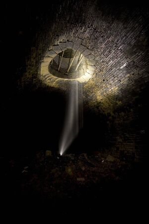 Falling water, Dark Tunnel ventilation shaft. Underground Light painting in disused railway tunnels, darkness creatively lit with torches. Stock Photo