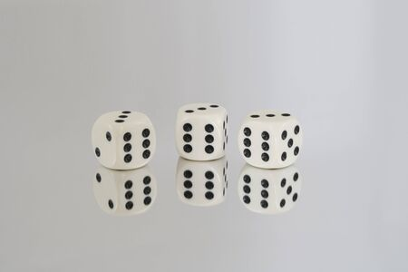 Three White dice with Black spots, all the 6s, and reflections.
