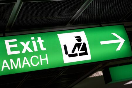 Green lighted Exit sign in airport with direction arrow. Stock Photo