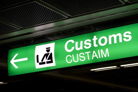 direction of the arrow: Customs sign in Airport and direction arrow, green and lighted.