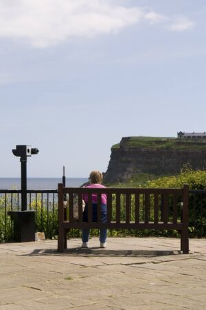 Woman on bench by telescope, looking out to see at Whitby, North Yorkshire UK