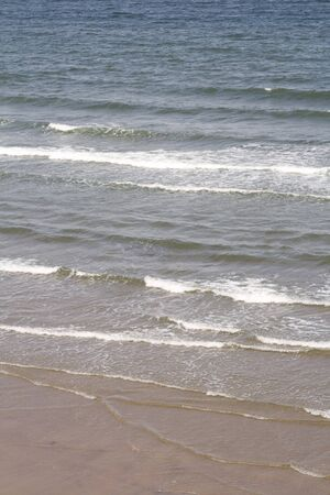 Gentle waves lapping the beach, seaside background, water texture. Stock Photo