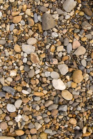 Seaside gravel and pebbles on the beach, beach background.