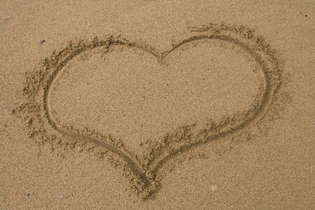 Love heart drawn in the sand. photo