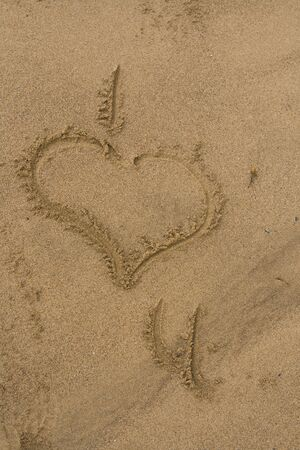 Love heart drawn in the sand. I heart you, I love you. Stock Photo