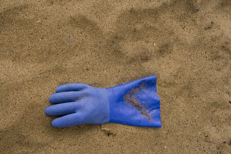Blue rubber glove on the sand at the beach.