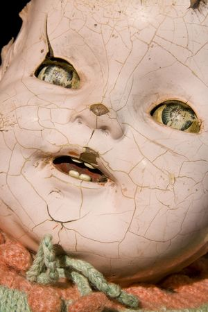 Old antique childs doll with creepy face, cracked and worn, has seen better days. Stock Photo - 4794341