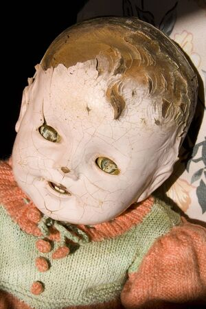 Old antique childs doll with creepy face, cracked and worn, has seen better days.