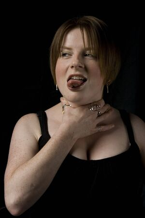 Girl with Black top and cross necklace set on black background, pulling silly face sticking tongue out with hand to throat. Stock Photo - 5885341