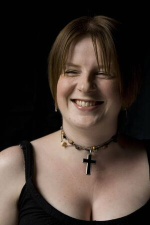 Girl with Black top and cross necklace set on black background. Stock Photo