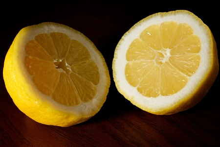 to cut: A lemon cut in half, exposing both sides on a table