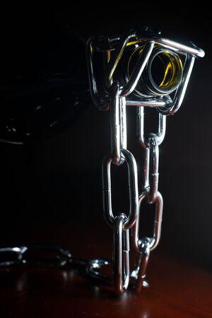 Side lit shot of a empty bottle held by a chain bottle holder