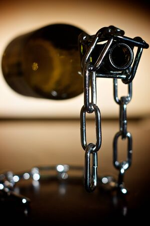 A emply wine bottle is held by a chain bottle holder