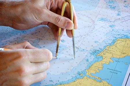 Persoon plot een fix op een papieren kaart Stockfoto