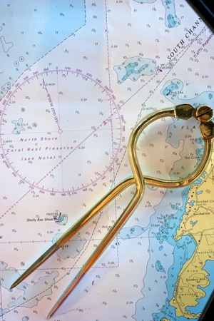 Brass dividers lay on a nautical chart of Bermuda photo