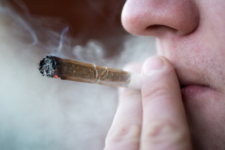 smoke: Man smoking marijuana cigarette soft drug in Amsterdam, Netherlands Stock Photo
