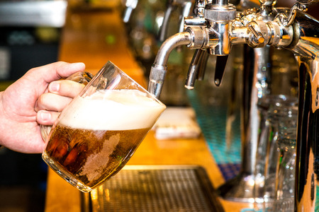 Close-up of barman hand at beer tap pouring a draught lager beer Фото со стока