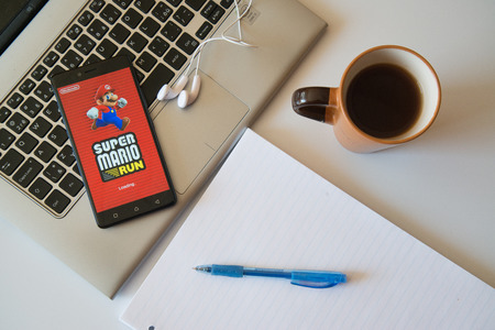 Nitra, Slovakia, march 28, 2017: Super Mario game application in a mobile phone screen. Workplace with a laptop, an earphones, notepad and coffee.