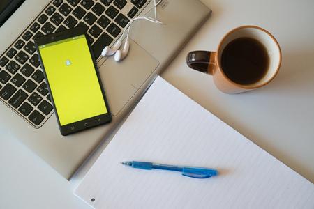 Nitra, Slowakije, 28 maart 2017: Snapchat applicatie in een mobiele telefoon scherm. Werkplaats met een laptop, een koptelefoon, een notitieblok en koffie. Redactioneel