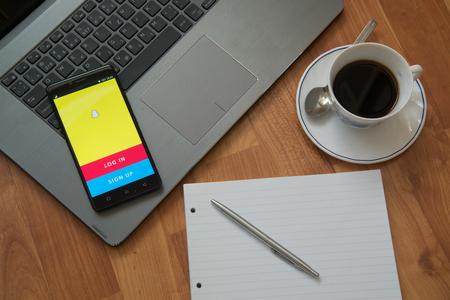 Nitra, Slowakije, 28 maart 2017: Snapchat-applicatie in het scherm van een mobiele telefoon. Werkplek met een laptop, een oortelefoons, Kladblok, pen en koffie op houten achtergrond