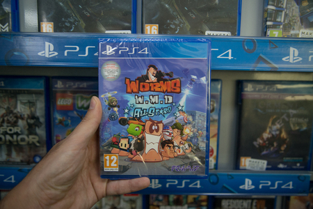 Bratislava, Slovakia, circa april 2017: Man holding Worms W.M.D. All stars videogame on Sony Playstation 4 console in store