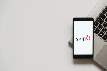 Bratislava, Slovakia, April 28, 2017: Yelp logo on smartphone screen placed on laptop keyboard. Empty place to write information. Editorial