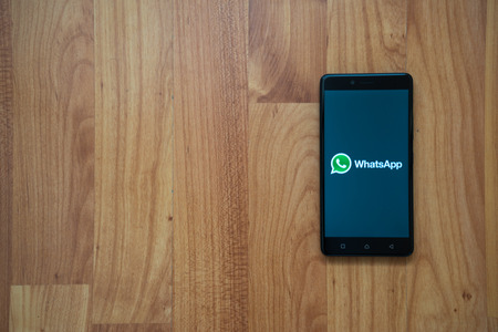 Los Angeles, USA, july 13, 2017: Whatsapp logo on smartphone screen on wooden background. Éditoriale