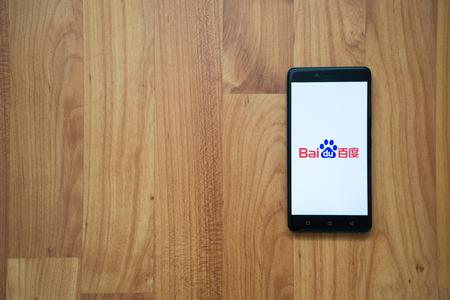 Los Angeles, USA, luglio 13, 2017: logo Baidu sullo schermo di smartphone su sfondo in legno. Archivio Fotografico - 83326737