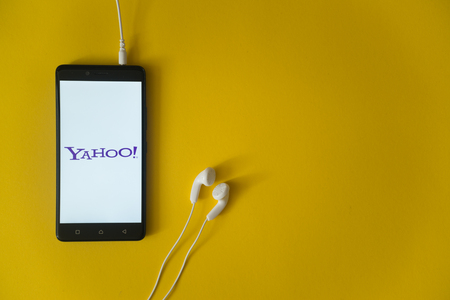 Los Angeles, USA, october 23, 2017: Yahoo logo on smartphone screen and earphones plugged in on yellow background.