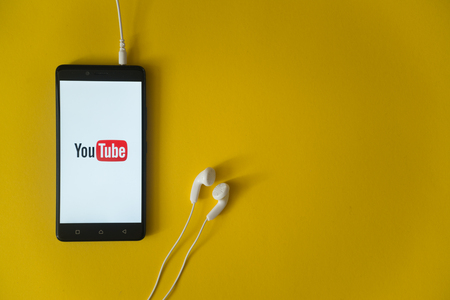 Los Angeles, USA, october 23, 2017: Youtube logo on smartphone screen and earphones plugged in on yellow background. Editorial