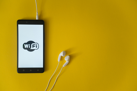 Los Angeles, USA, october 23, 2017: Wifi logo on smartphone screen and earphones plugged in on yellow background. Redakční
