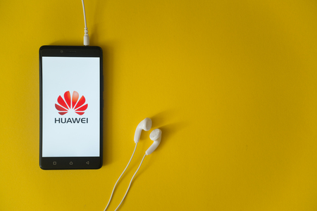 Los Angeles, USA, october 23, 2017: Huawei logo on smartphone screen and earphones plugged in on yellow background. Редакционное