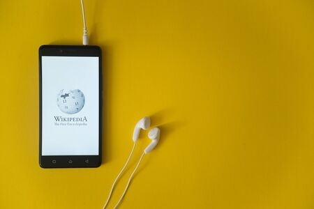 wiki wikipedia: Los Angeles, USA, october 23, 2017: Wikipedia logo on smartphone screen and earphones plugged in on yellow background. Editorial
