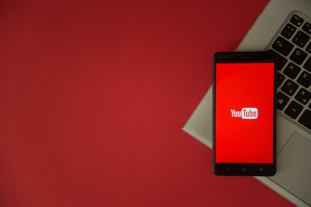 London, United Kingdom, October 23, 2017: Youtube logo on smartphone screen placed on laptop keyboard. Empty place to write information with red background.