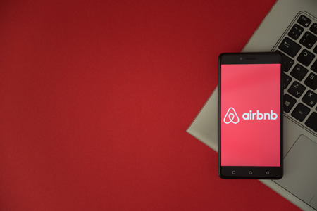 London, United Kingdom, October 23, 2017: Airbnb logo on smartphone screen placed on laptop keyboard. Empty place to write information with red background.