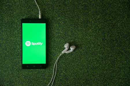 Los Angeles, USA, october 23, 2017: Spotify logo on smartphone screen on green grass background. Redakční