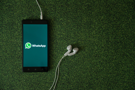 Los Angeles, USA, october 23, 2017: Whatsapp logo on smartphone screen on green grass background.