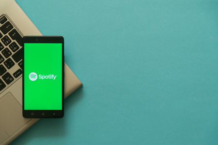 Los Angeles, USA, october 19, 2017: Spotify logo on smartphone placed on laptop keyboard. Empty copyscape place on green background to write information. Editorial