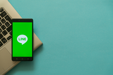 Los Angeles, USA, october 19, 2017: Line logo on smartphone placed on laptop keyboard. Empty copyscape place on green background to write information. Editorial