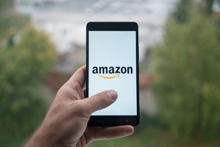 London, United Kingdom, october 3, 2017: Man holding smartphone with Amazon logo with the finger on the screen Éditoriale