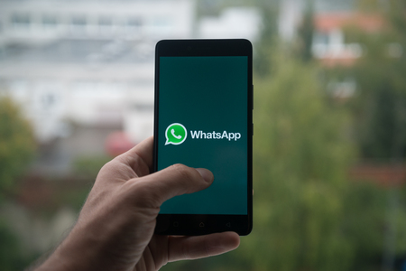 London, United Kingdom, october 3, 2017: Man holding smartphone with Whatsapp logo with the finger on the screen Stock Photo - 88738959