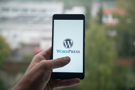 London, United Kingdom, october 3, 2017: Man holding smartphone with Wordpress logo with the finger on the screen Фото со стока - 88738975