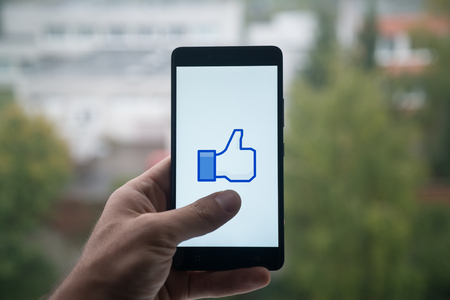 London, United Kingdom, october 3, 2017: Man holding smartphone with Facebook like logo with the finger on the screen Editorial