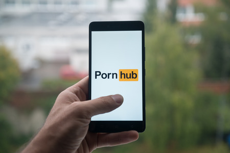 London, United Kingdom, october 3, 2017: Man holding smartphone with Pornhub logo with the finger on the screen