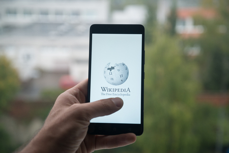 wiki: London, United Kingdom, october 3, 2017: Man holding smartphone with Wikipedia logo with the finger on the screen