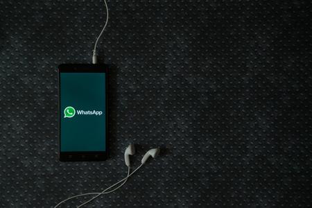 Los Ángeles, los EEUU, el 23 de octubre de 2017: Logotipo de Whatsapp en la pantalla del teléfono inteligente y auriculares enchufados en fondo plateado de metal. Foto de archivo - 88872294